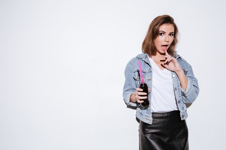 aerated: Image of a young pretty lady dressed in jeans jacket standing isolated over white background while drinking aerated sweet water.