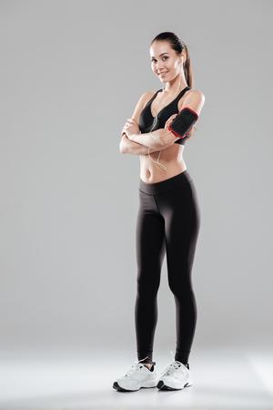 De volledige lengte van glimlachende zekere jonge sportvrouw die zich met wapens bevinden kruiste over grijze achtergrond
