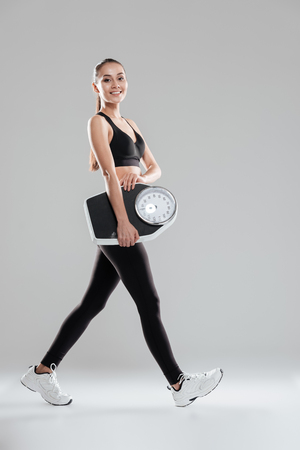 Happy cute young woman athlete walking and holding weighing scale over gray background