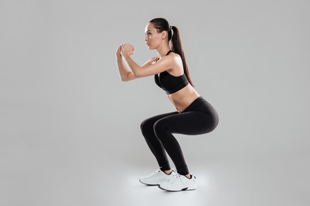 Full length of concentrated young woman athlete doing squats over gray background Stock Photo - 70949861