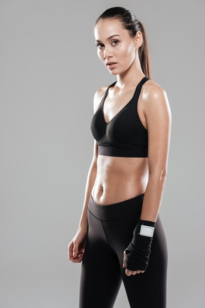 Portrait of beautiful young woman athlete with boxing wraps on her hand over gray background