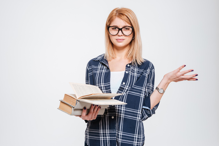 Image of confused young lady reading books isolated on a white background.