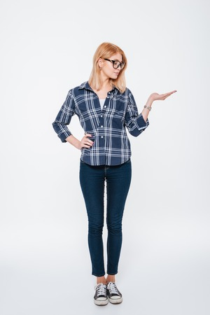 Picture of a pretty woman wearing eyeglasses posing isolated on a white background and holding copyspace in hand.