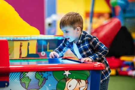 Happy little boy standing and playing air hockey game at amusement park