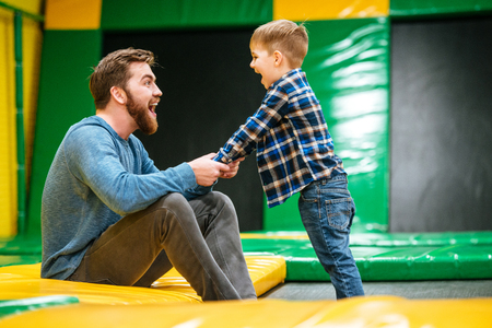 bets: Cheerful dad and son having fun and playing together at indoor playground