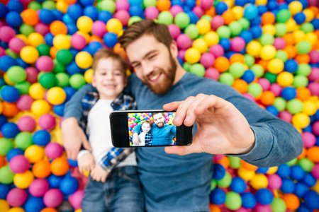 Joyful little boy and dad lying in colorful balls pool and making selfie with mobile phone