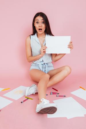 Geschokte jonge vrouw die lege raad houdt terwijl het zitten op een vloer die op roze achtergrond wordt geïsoleerd