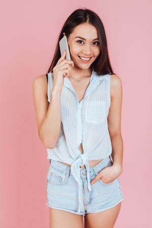 Charming young woman talking on cell phone isolated on a pink background