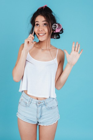 Image of attractive young lady with hair curlers isolated over blue background talking by phone