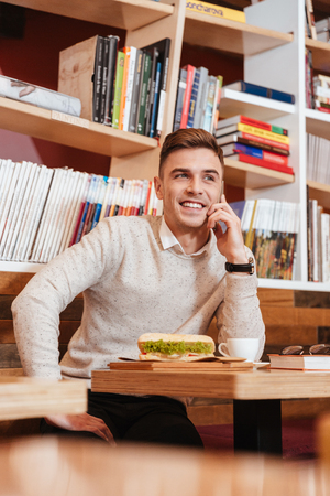 aside: Picture of young cheerful man sitting in cafe while talking by his mobile phone. Stock Photo