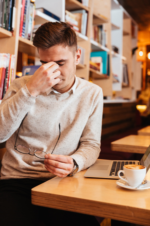 touching noses: Image of tired young man sitting in cafe and using laptop while touching his eyes