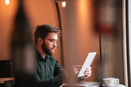 Photo de séduisante jeune homme barbu portant des lunettes, assis au café tout en utilisant la tablette tactile.