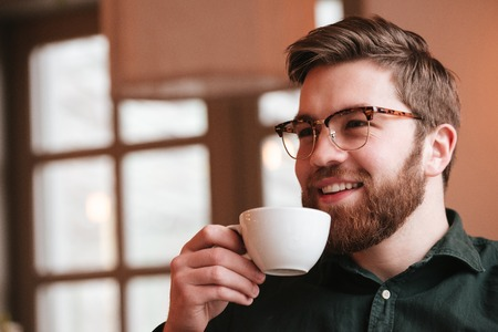 tabla de surf: Image of happy bearded young man wearing glasses sitting in cafe while drinking coffee.