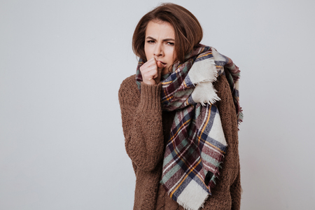 sweatshirt: Freeze woman in sweater and scarf holding hand near the mouth and looking at camera. Isolated gray background