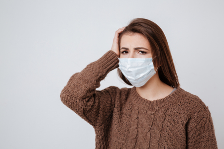 Woman in sweater and medical mask holding her head and looking at camera. Isolated gray background Stock Photo