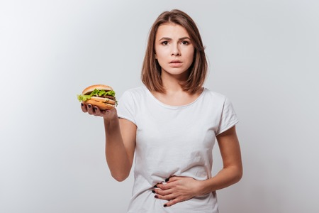 Image of confused young woman with painful feelings standing over white background while holding fastfood and touching belly Stock Photo