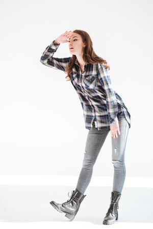 立っていると遠くに白い背景を見ているかなり若い女性の完全な長さ