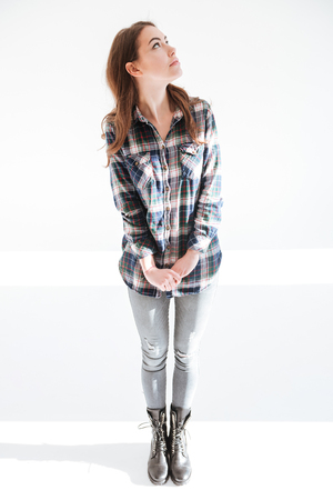 Full length of cute young woman in plaid shirt standing and looking away over white background Stock Photo