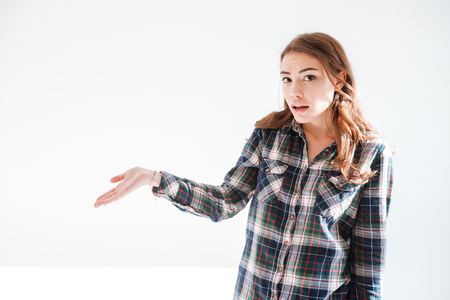 indecisive: Amazed confused young woman in plaid shirt holding copyspace on palm over white background
