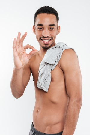 Image of cheerful african man posing over white background and make okay gesture. Stock Photo