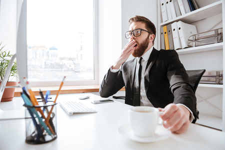 Image of handsome bearded businessman sitting in office while holding coffee and yawning