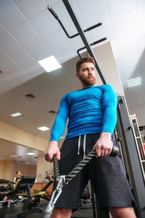 flare up: Photo of handsome young sportsman make sport exercises while standing in gym and looking aside.
