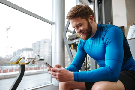Image of cheerful young sportsman sitting in gym and looking at phone.