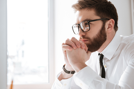 Picture of serious young businessman wearing glasses dressed in white shirt sitting in office and looking at computer. Stock Photo