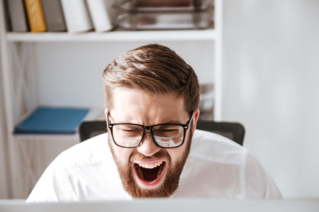 Photo of screaming angry young businessman wearing glasses dressed in white shirt sitting in office and looking at computer. Stock Photo