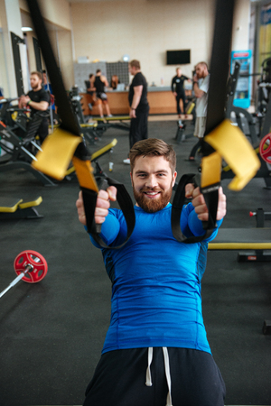 flare up: Image of handsome young sportsman in gym make sport exercises. Looking at camera.