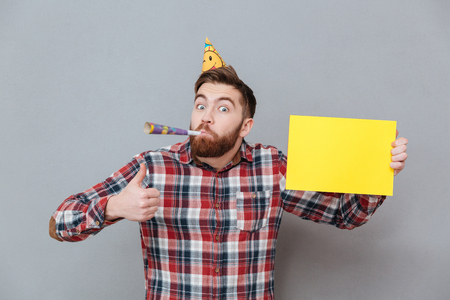 big shirt: Image of happy young bearded birthday man holding copyspace board make thumbs up gesture standing over grey background.