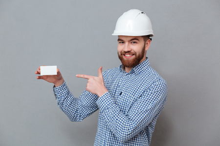 Picture of cheerful bearded builder holding copyspace business card and pointing standing over grey background.