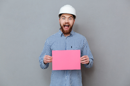 Picture of happy bearded man builder holding copyspace blank standing over grey background.