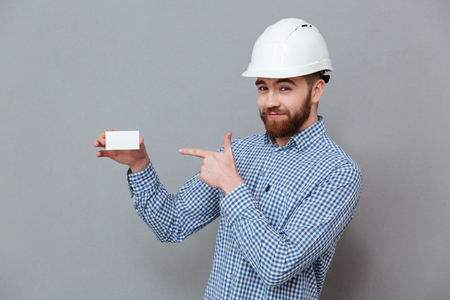 Photo of cheerful bearded builder holding copyspace business card and pointing standing over grey background.
