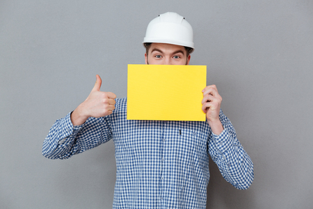Image of handsome young bearded man builder holding copyspace blank make thumbs up gesture standing over grey background. Stock Photo