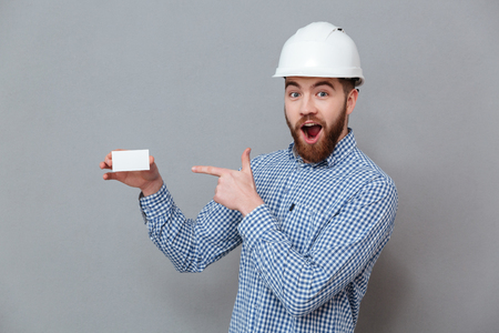 Image of shocked bearded builder holding copyspace business card and pointing standing over grey background. Stock Photo