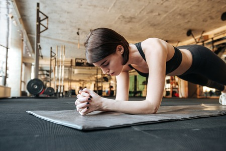 body built: Focused young fitness woman doing plank exercise in gym