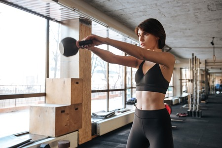 exercices: Concentrated young fitness woman doing exercices with kettleball in gym Stock Photo