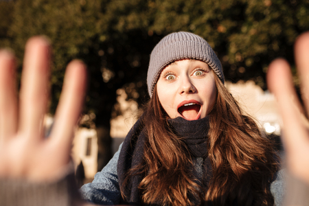 Amazed scared young woman showing stop gesture with both hands in the city