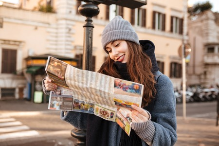 Smiling concetrated young woman using map and walking in the city Stock Photo