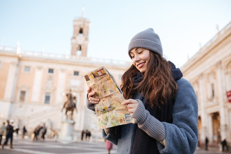 Happy cute young woman standing and using map in old city Banco de Imagens