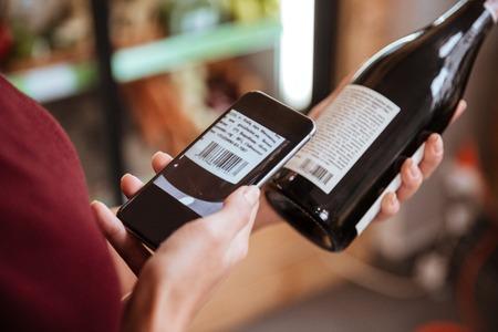 食料品店でワインの瓶の携帯電話でバーコードをスキャン女性のクローズ アップ