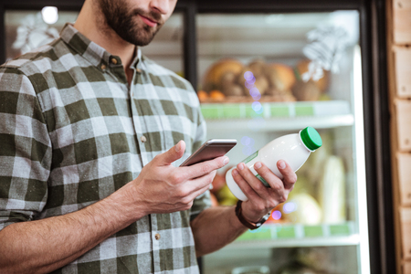 Hansome bearded young man with bottle of milk using mobile phone at grocery shop