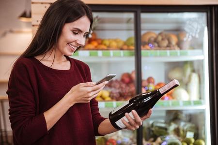 Lachende jonge vrouw kiezen wijnstok en scannen barcode op de fles in de supermarkt