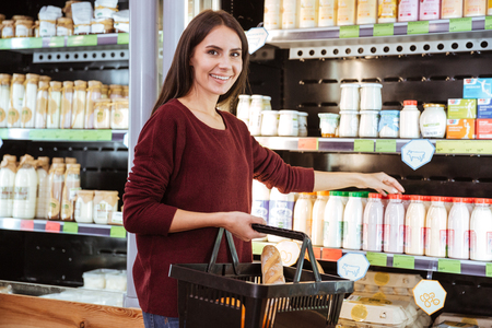 Happy attractive young woman with basket doing shopping and buying yoghurt in grocery store