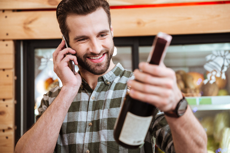 Happy young man buying wine and talking on cell phone in grocery shop Stock Photo