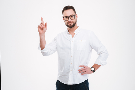 Photo of serious young bearded man dressed in white shirt wearing glasses pointing at copyspace isolated over white background.
