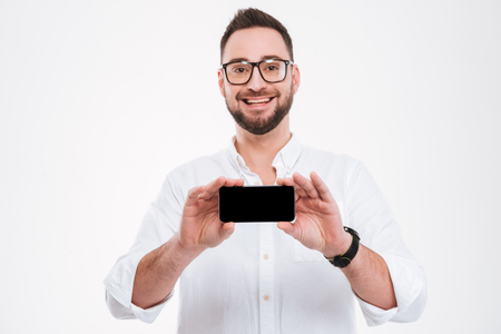 Image of smiling young bearded man wearing glasses dressed in white shirt showing phone display to camera isolated over white background. Stock Photo
