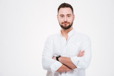 Image of handsome bearded man dressed in white shirt posing with arms crossed isolated over white background.
