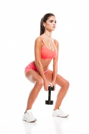 en cuclillas: Full length portrait of a sexy young fitness woman doing squatting with heavy dumbbell isolated on a white background